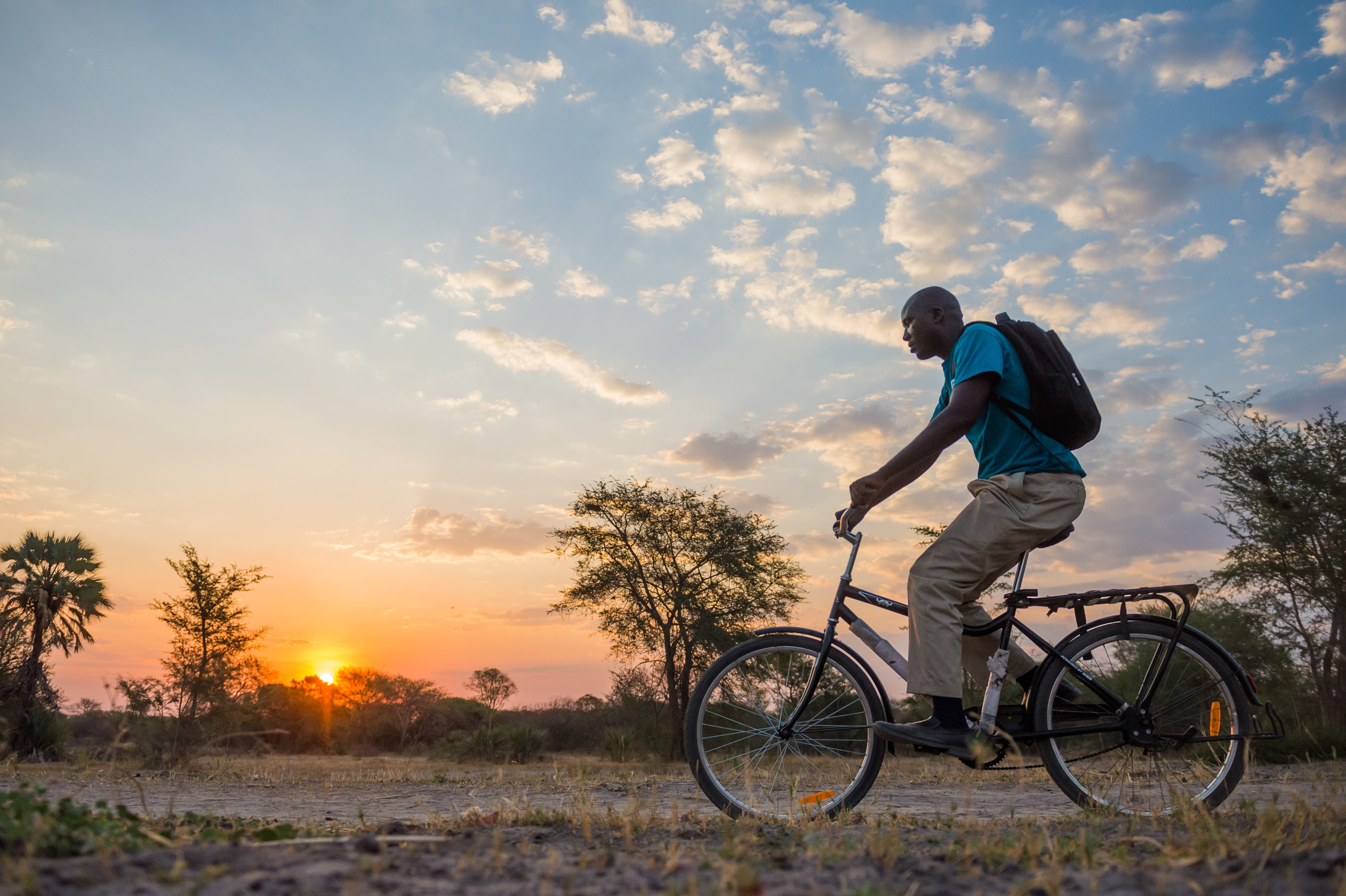 A community health worker rides his bike