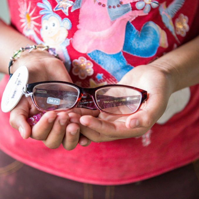 A girl holds glasses in her hands