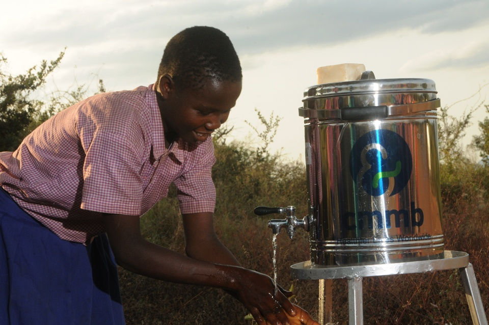 Anastasia washing hands in Kenya with clean water from CMMB-provided water dispenser.