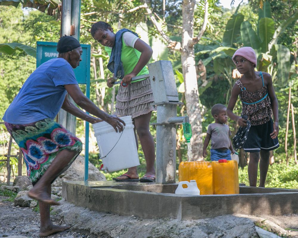 A family collects clean water at a borehole well in Haiti in July 2020