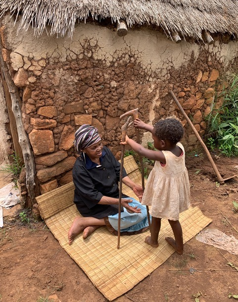 A home-based care patient sits outside her home in Swaziland