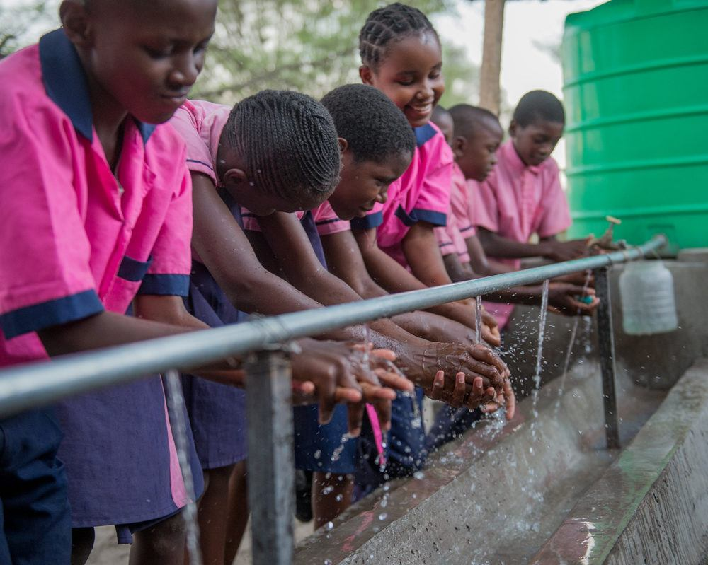 Students in Pink Unifroms Washing Hands with Clean Water in Mwandi, Zambia in October 2019