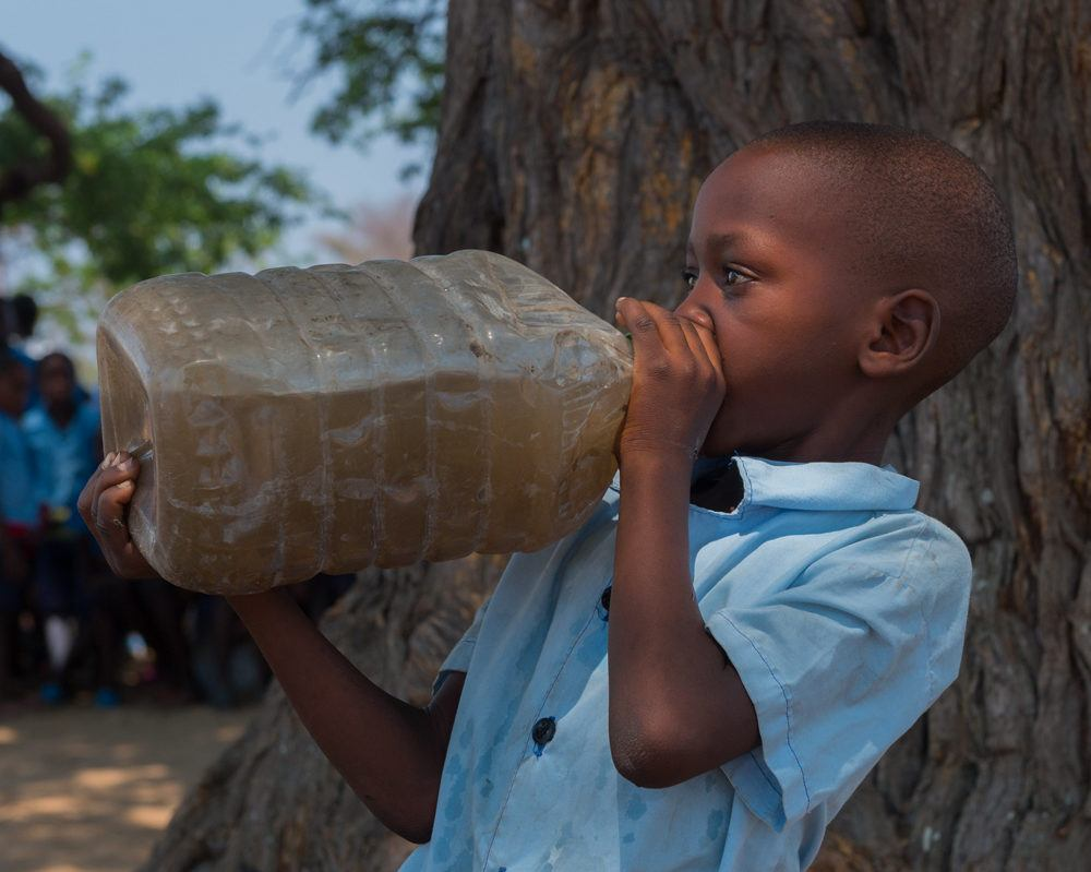 Young Boy Drinking Unclean Water from Bottle in Mwandi Zambia in October 2019