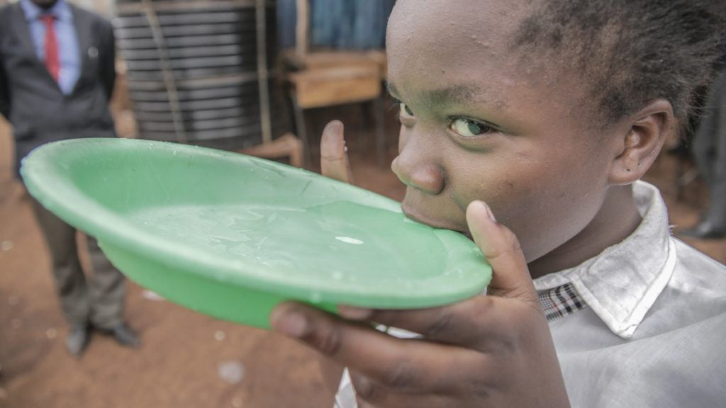 Young Girl Drinking Clean Water from Green Container in Kenya in 2017