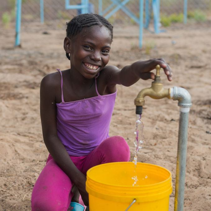 Young Girl with Clean Water Pouring from Faucet into Bucket