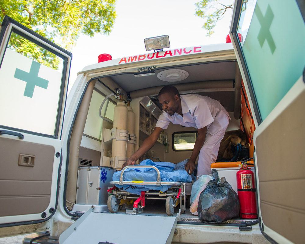 A first responder health care worker removes a stetcher from an ambulance in Zambai in December 2015