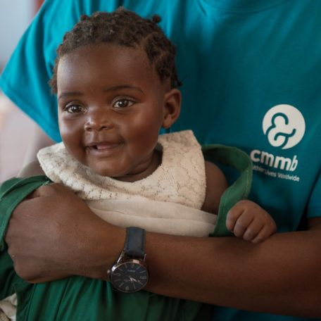 A baby girl being held by a community health worker in Mwandi, Zambia in October 2019.
