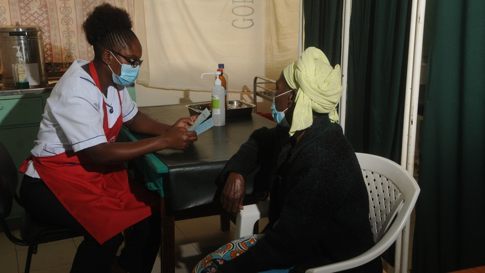 A healthcare worker with a patient before a cervical cancer screening in Kenya in June 2020.