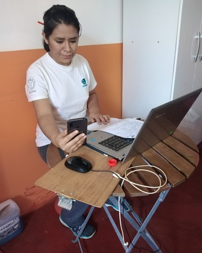 A community health worker before a computer with a phone during COVID-19 reaching the community through telecounseling in June 2020.
