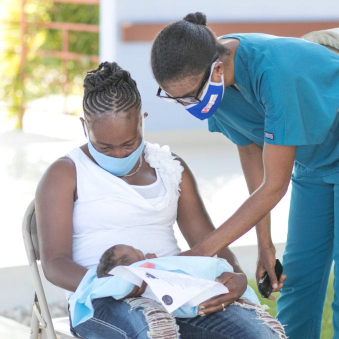 Community healthcare worker at Bishop Joseph Sullivan Hospital with mother and child in Haiti in July 2020.