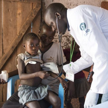 A doctor checks the temperature of a child sitting on mother's lap in internally displaced persons camp in Rimenze, South Sudan in December 2017.