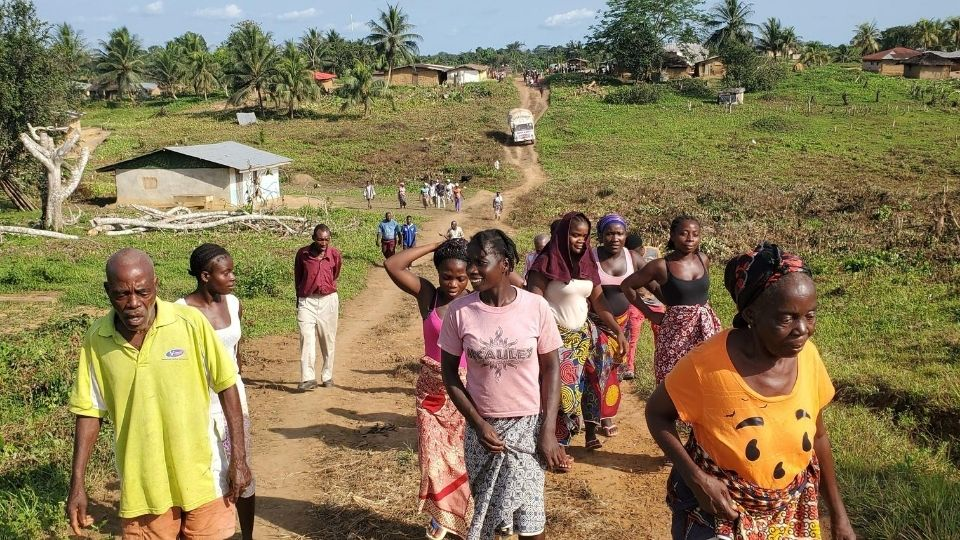 A group of people walk down a dirt road in a village of Liberia