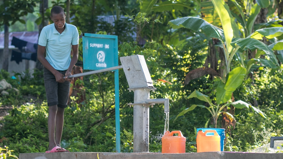 A boy collects clean water from a borehole well in Haiti in July 2020.