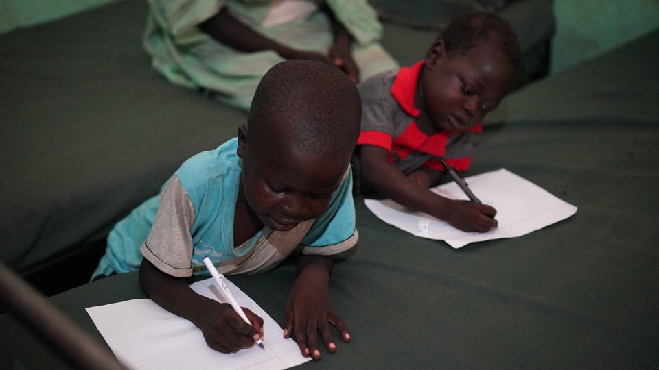 Two children writing who are being treated for malnutrition at Mother of Mercy Hospital in Sudan in June 2018.