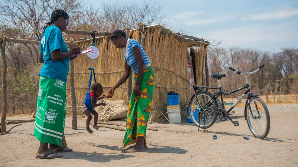 A community health worker with a mother and her child being weighed for malnourishment in Zambia in October 2019.