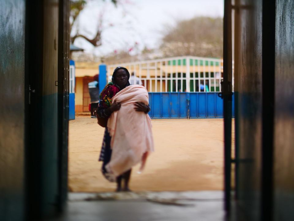 A mother holding her child walks into the Mutmo Mission Hospital in Kenya in 2018