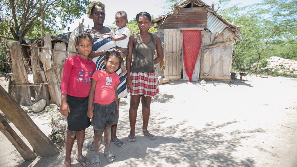 A poor haitian family stand before their home in July 2020.