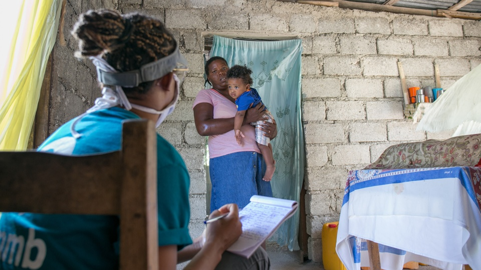 A community health worker with a mother and child during COVID-19 response in Haiti in July 2020.