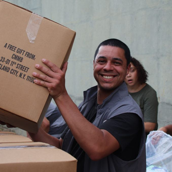 Medical Donations Program logistics staff member holding a box relief during a kitting event at the distribution center in New York in October 2019.