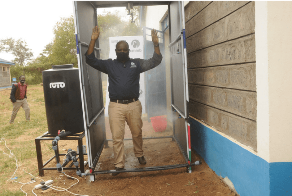 Health worker stands in sanitation booth at Kitui South's treatment center in Kenya