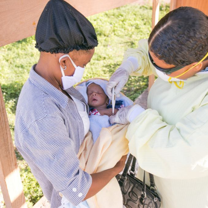 A mother holding her infant child as a community healthcare worker in Haiti assist for COVID-19 in Haiti in July 2002.