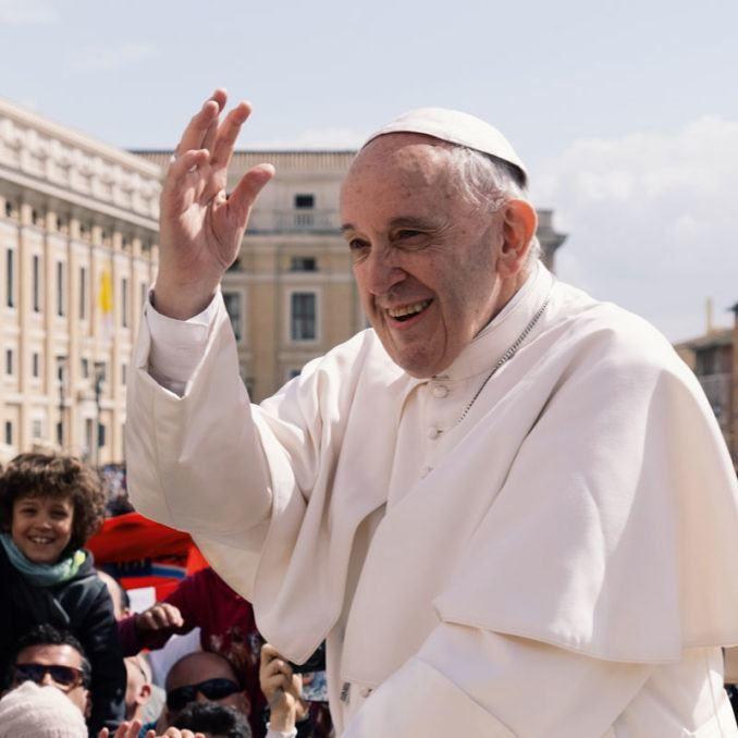 Pope Francis smiling and waving to a crowd in Vatican City in 2018.