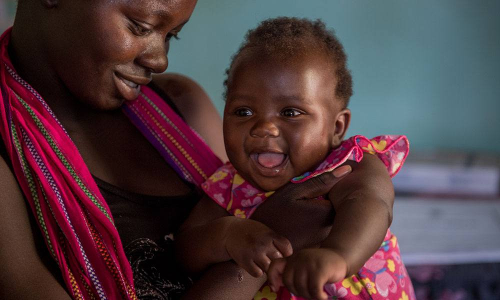 A mother with her smiling baby girl in Mwandi, Zambia in October 2019.
