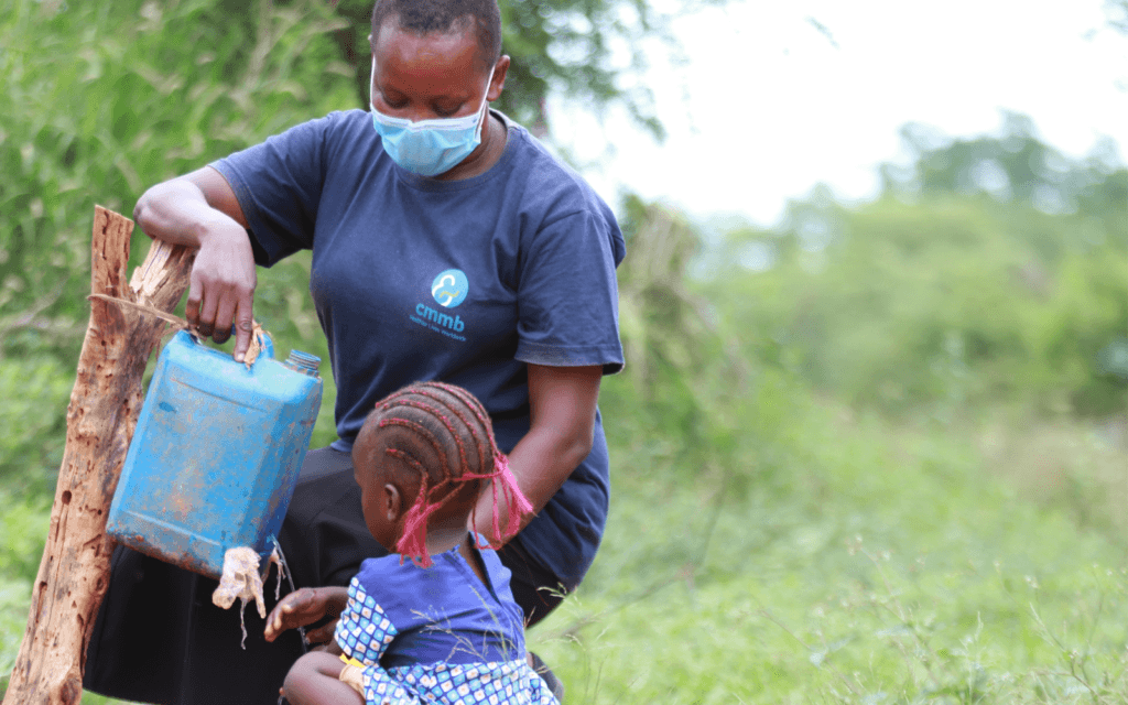 Community Health Worker Ndunge with child