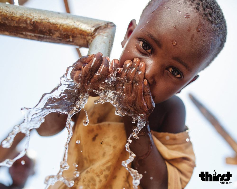 Thirst Project - A child drinking water from a faucet in Eswatini.