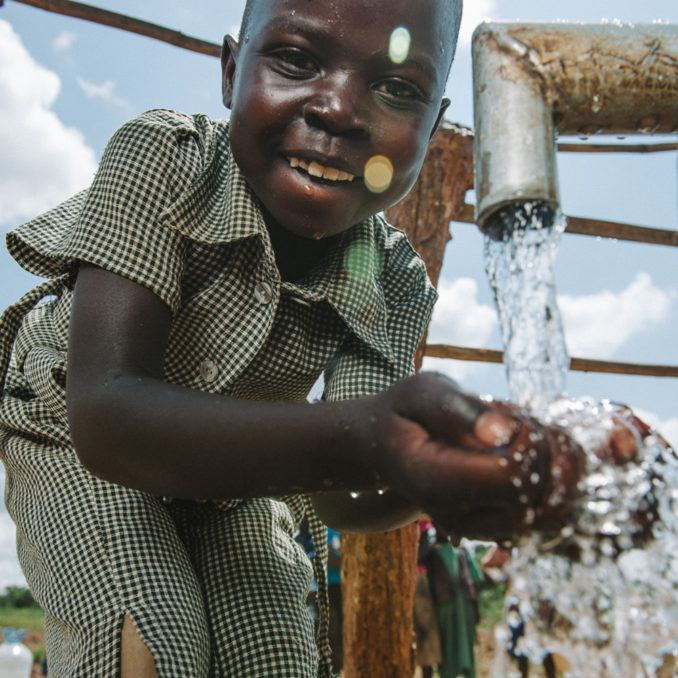 Thirst Project - A child drinking water from a faucet in Uganda..