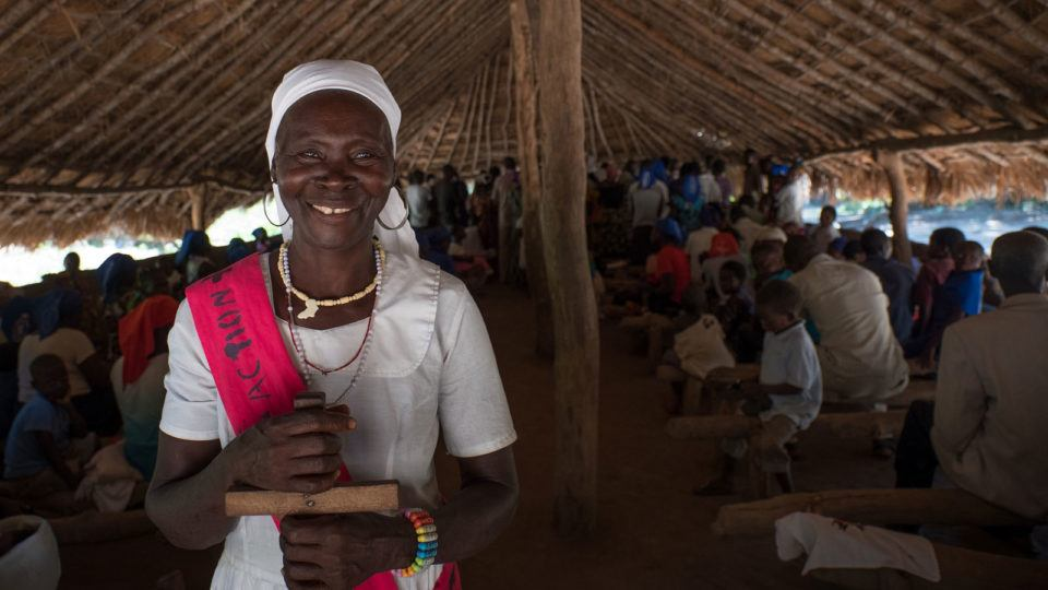 A woman smiling with a cross during churhc service in South Sudan in October 2018.