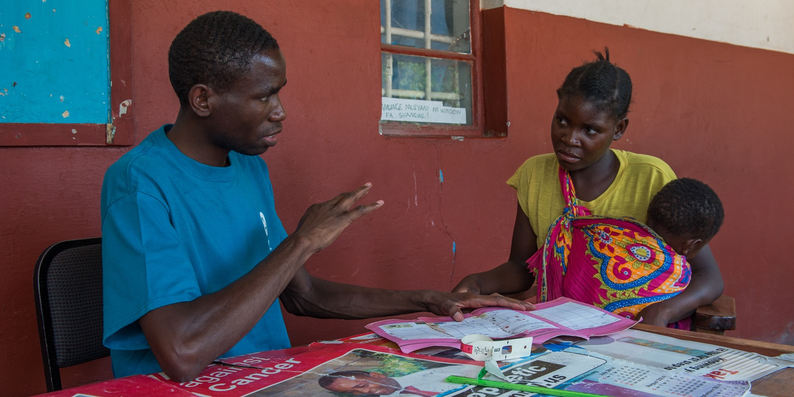 CMMB program coordinator Mwauluka speaking with a mother and her child in Mwandi, Zambia.
