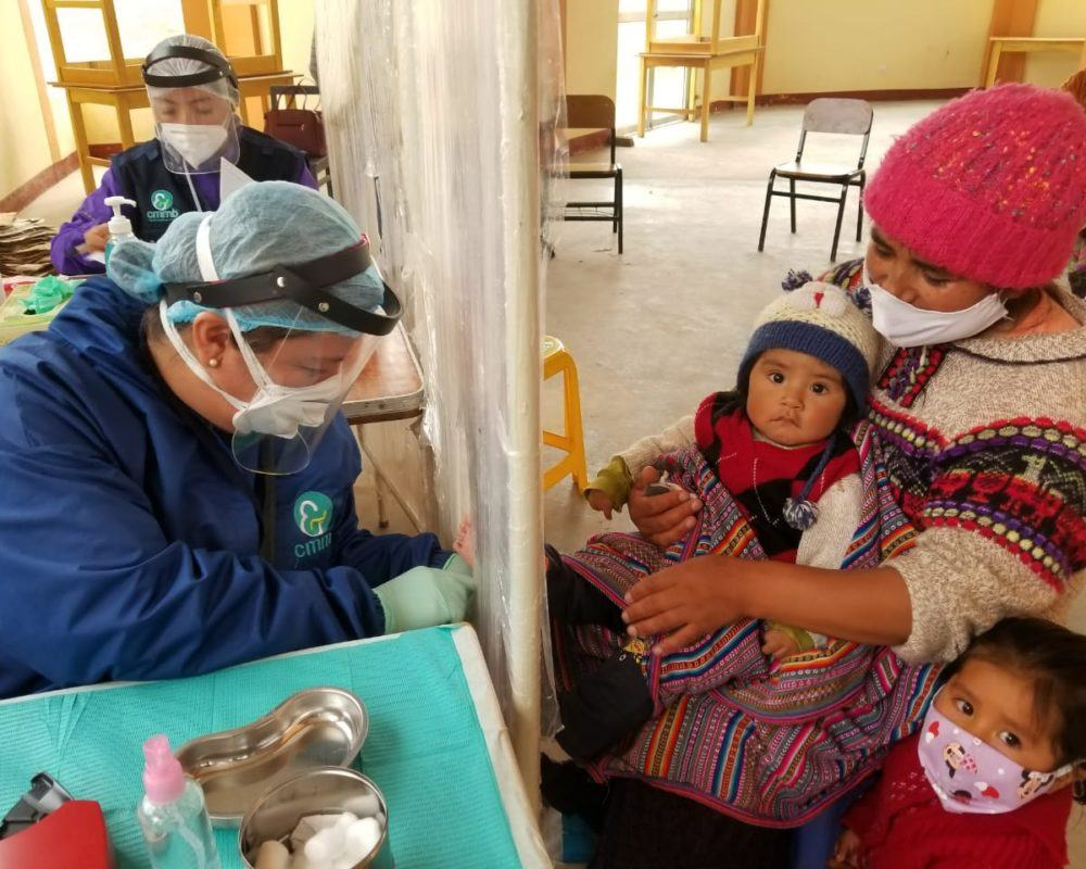 A community health worker providing care to a mother and her children during COVID-19 in Peru.