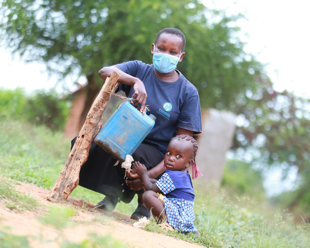 A community health worker wearing a face mask with a young girl at a tippy tap for clean water in Kenya in 2021.