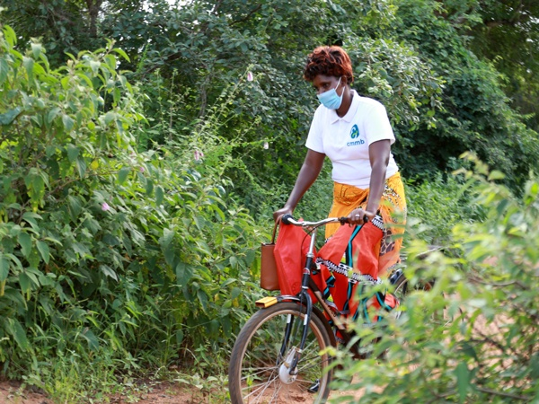A community health worker wearing a face mask on a bicycle in Kenya in 2021.