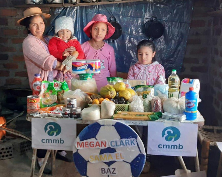 A mother with her young children stand before a survival care package for COVID-19 provided by CMMB in Peru in 2021.