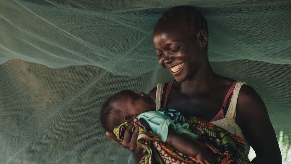 Mom smiles while holding her baby_South Sudan