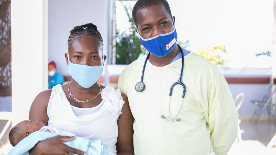 A mother holding her newborn infant with a doctor at Bisop Joseph Sullivan Center for Health hospital in Haiti in 2020.