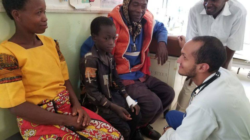 Dr. Jose speaks to a young patient in Kenya in 2019