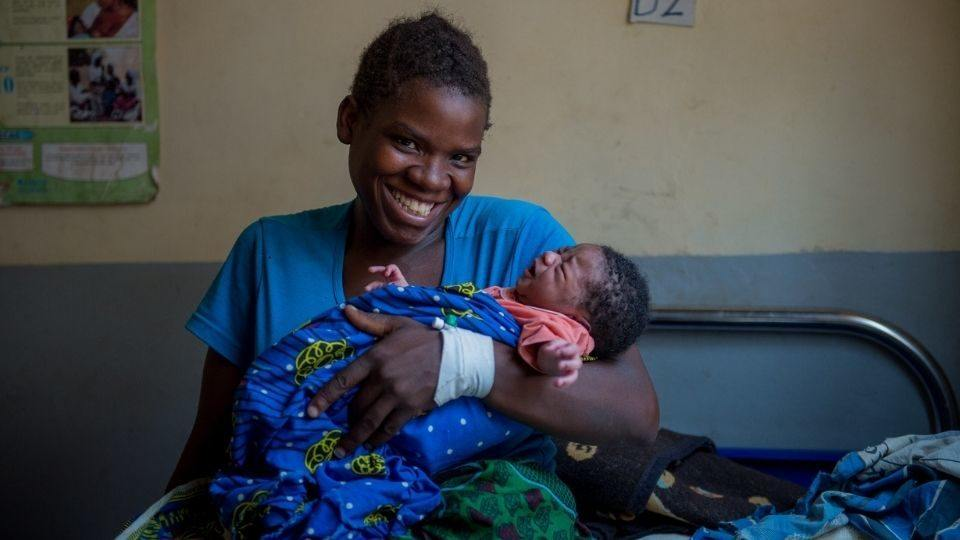 A mom an infant are treated at at rural health facility in Mwandi