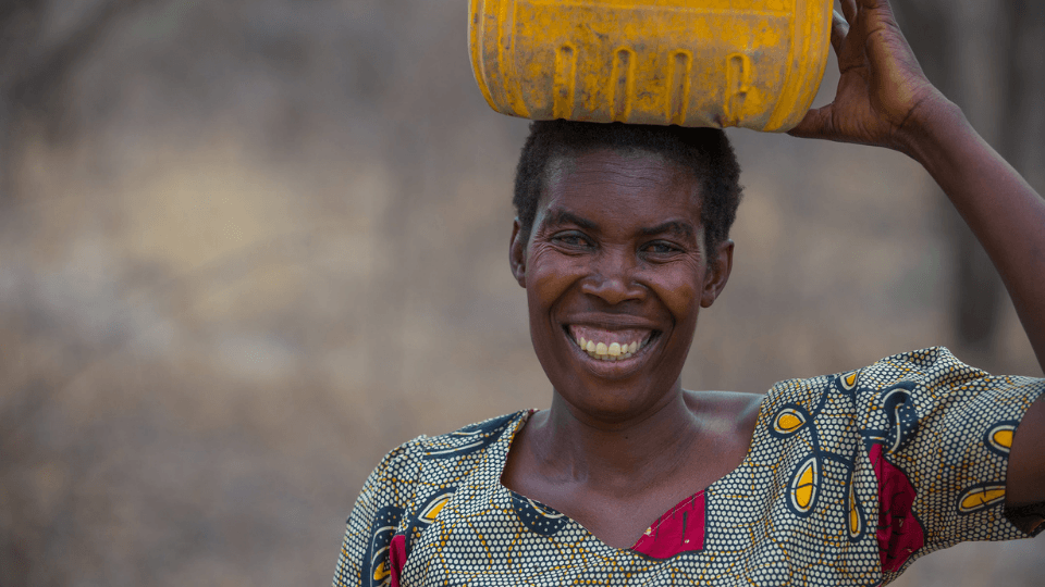 A woman carries water in a jerrycan in Zambia