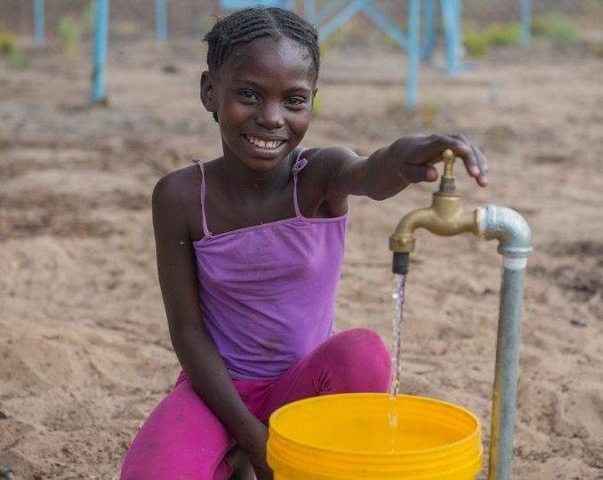 A young girl uses a borehole at her primary school in Zambia