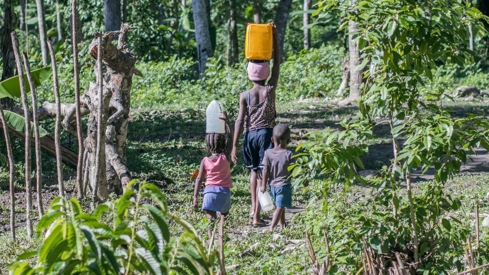 A woman and her children walk to collect water in Haiti