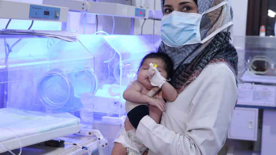 A health worther at Al-Rahma Hospital in northwest Syria hold a newborn infant in 2021.