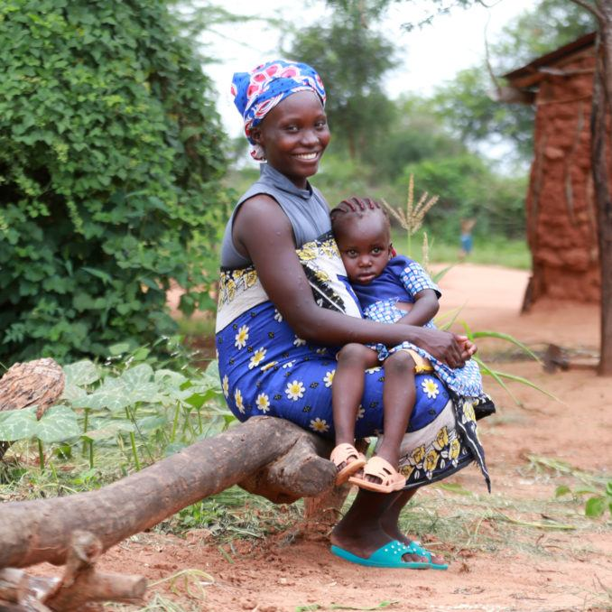 A mother in rural Kenya with her daughter sitting on her lap in 2021.