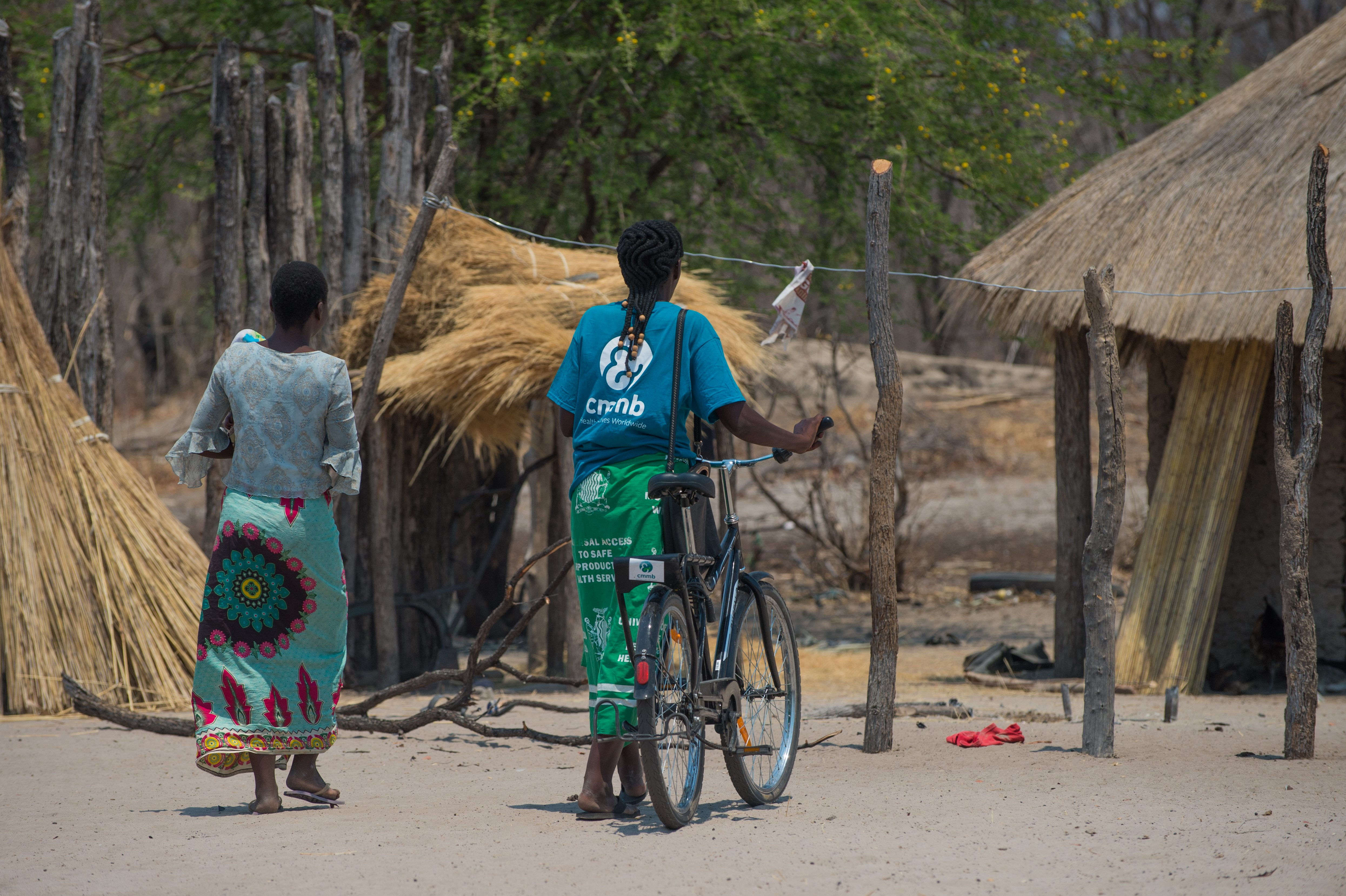 community health worker with bicycle and mother in zambia