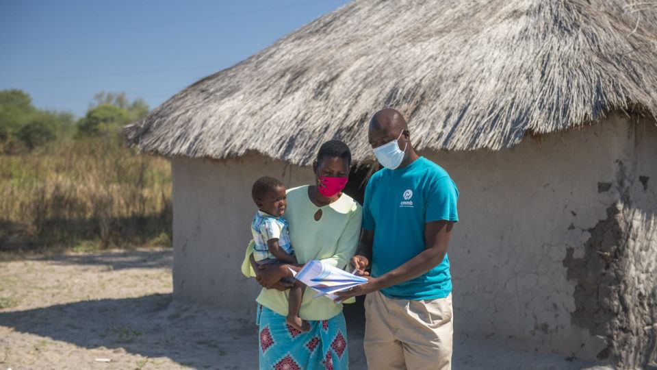 community health worker with mother and child in front of facility in zambia