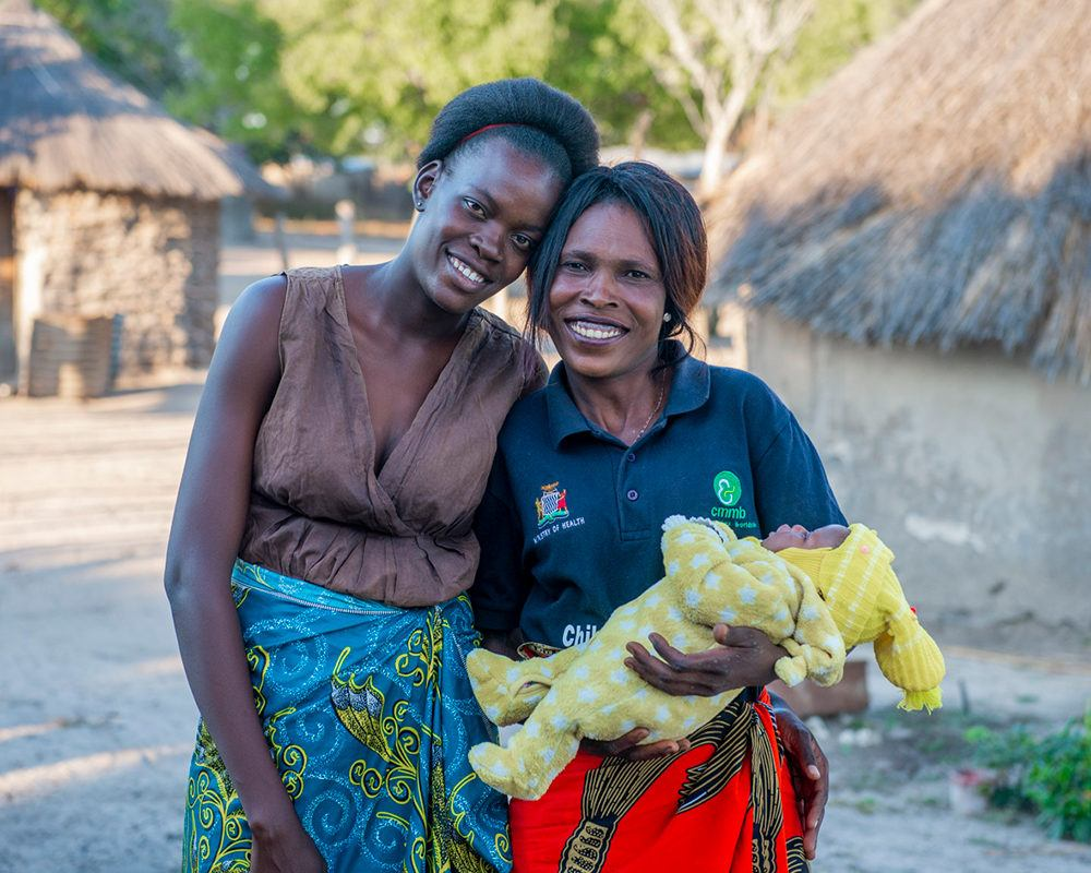 A mother with a community health worker holding an infant in rural Mwandi, Zambia in June 2021.