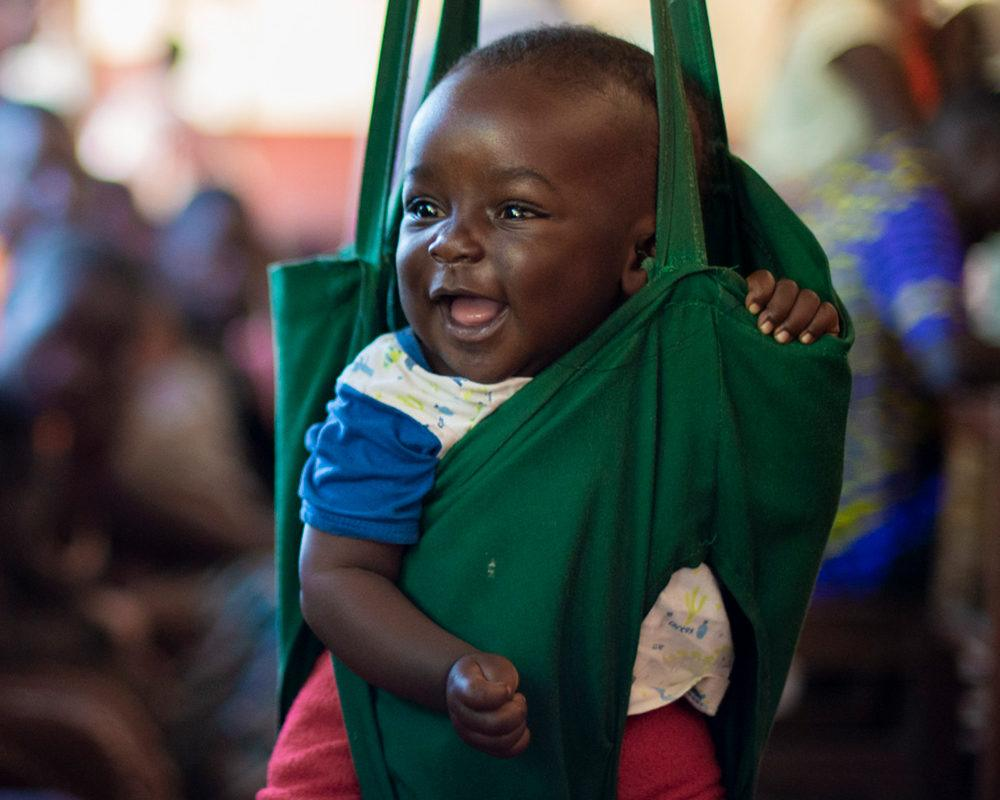 A smiling baby being weighed by a community health worker in Mwandi, Zambia in June 2021.
