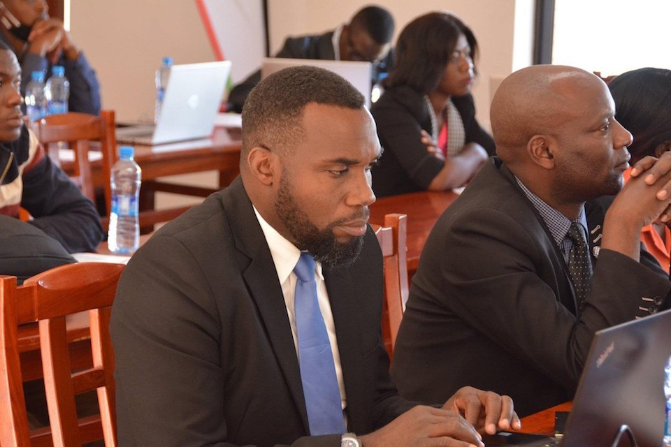 Henry Mshoka sits with colleagues